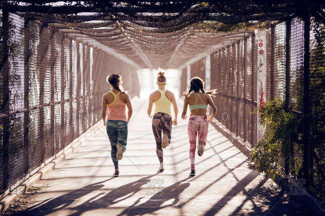Female joggers on a pedestrian bridge