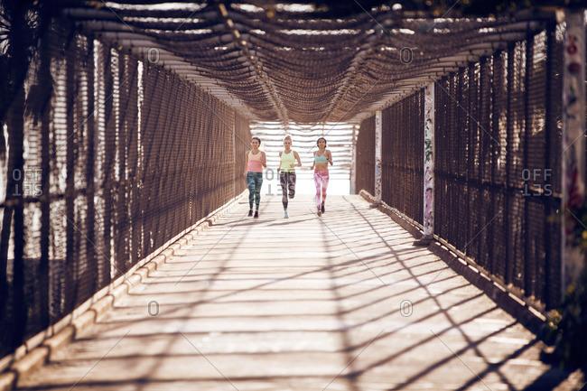 Group of women running on a pedestrian bridge