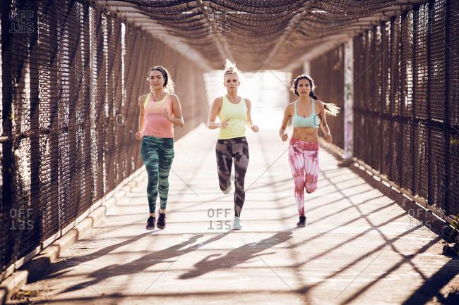 Women running together on a pedestrian bridge