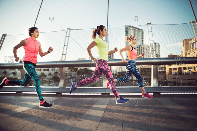 Group of women running on a bridge