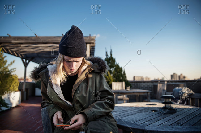Teenage boy on rooftop patio with smartphone