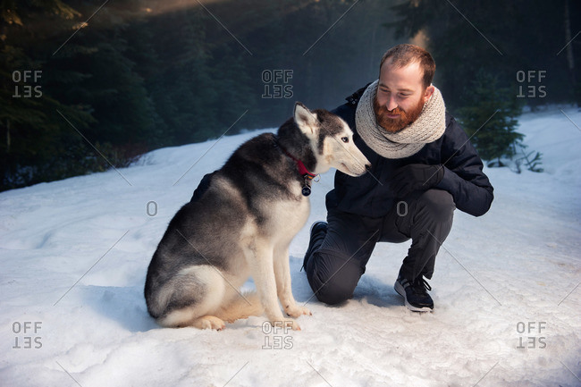 Man with a Siberian Husky in winter in Frog Lake, Oregon