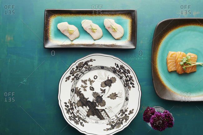 Plates and raw fish on a turquoise table top