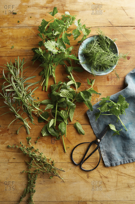 Variety of fresh herbs on a wooden board