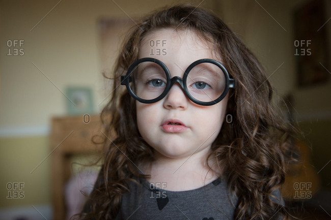Young girl wearing big round glasses