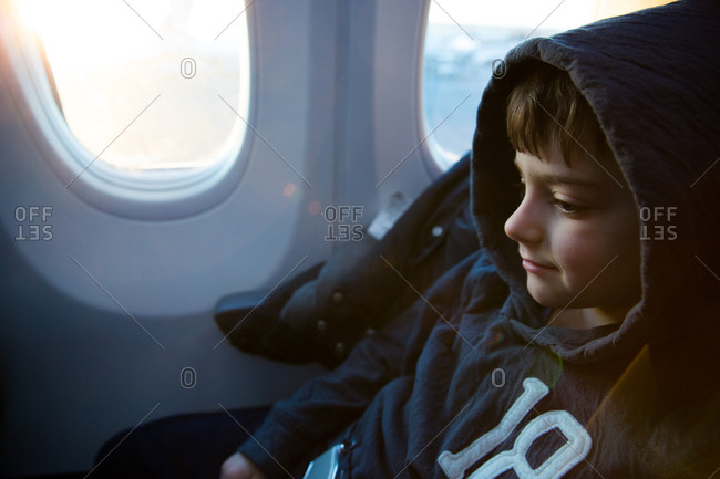 Boy in hoodie on an airplane