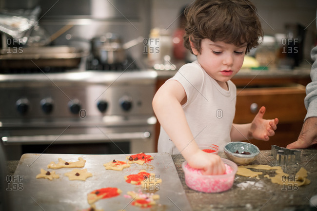 Young boy decorating Christmas cookies with sprinkles