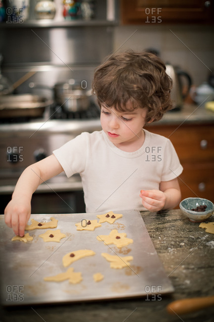Young boy decorating Christmas cookies with chocolate chips