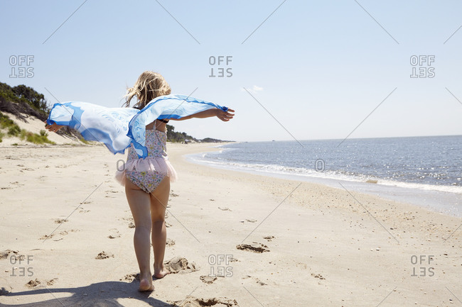Girl running with beach shawl
