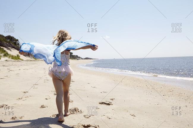 Girl running with beach shawl