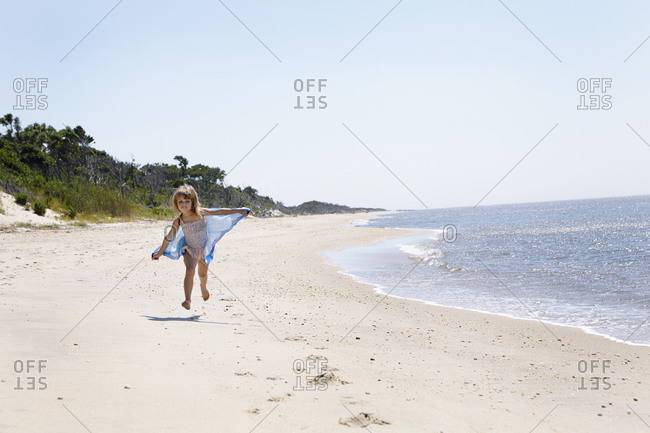 Girl running on beach with a shawl