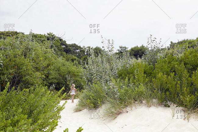 Girl walking into a beach path