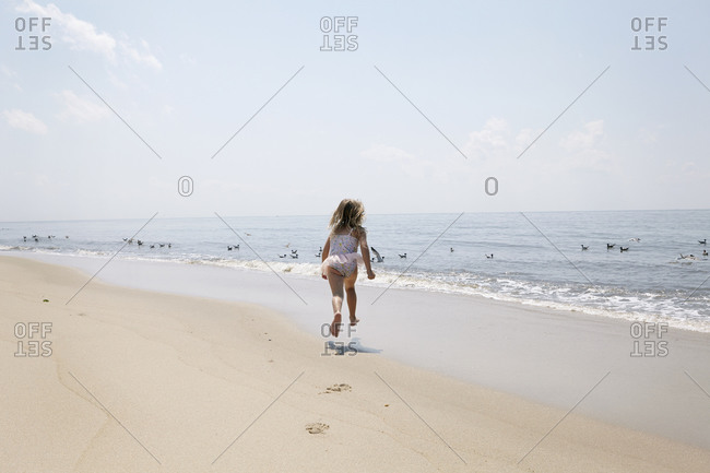 Girl running on beach towards birds