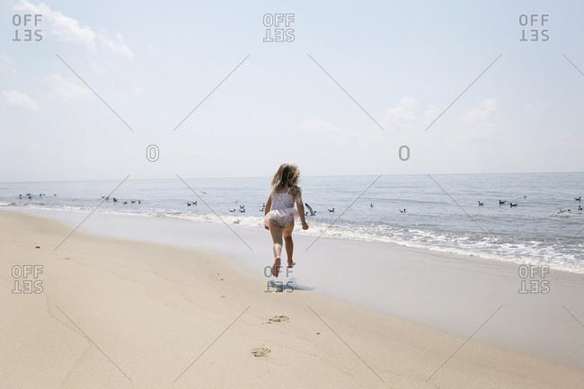 Girl running on beach towards birds