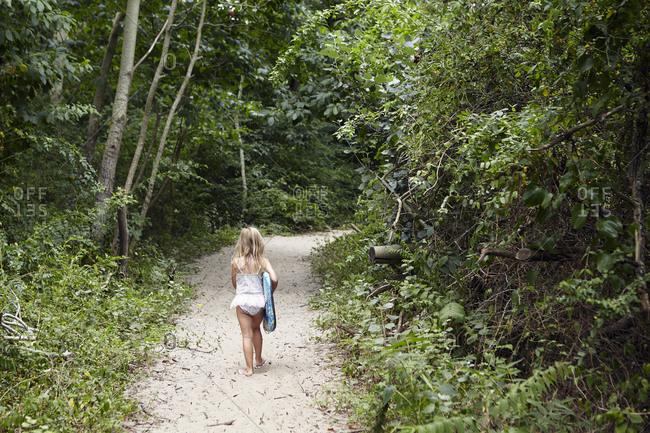 Girl with body board on beach path