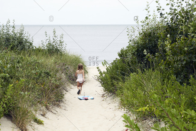 Girl dragging body board towards beach
