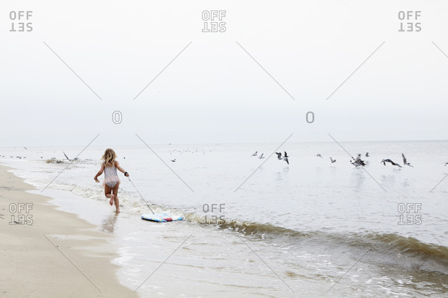Girl running on beach dragging board