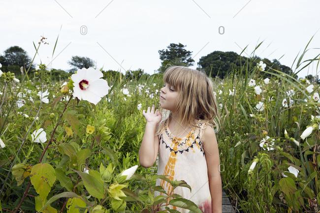 Girl among coastal flowers