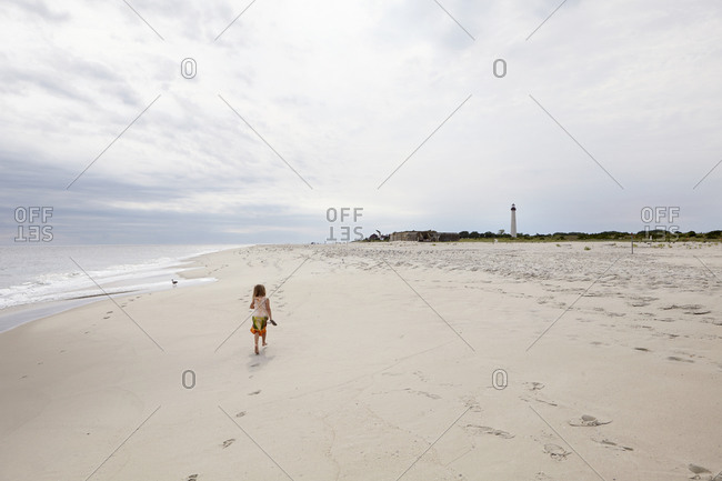 Girl walking down beach coastline