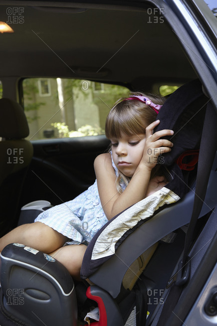 Girl lying sleepily in car seat