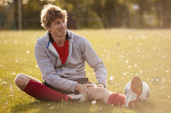 Smiling young soccer player massaging leg while sitting on field
