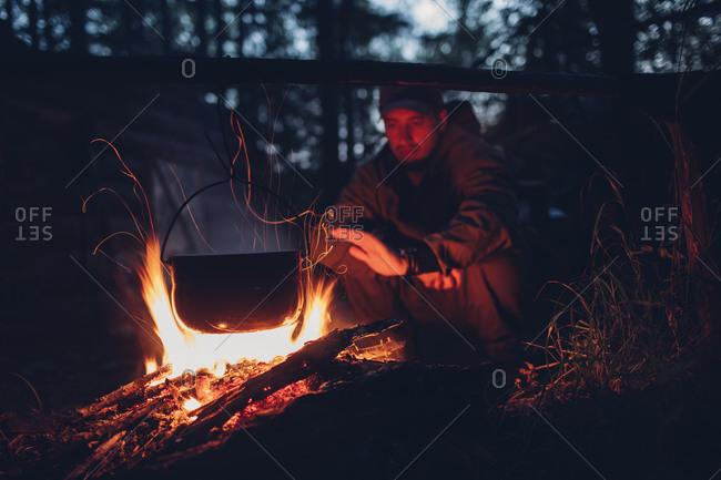 Man warming hands at campsite