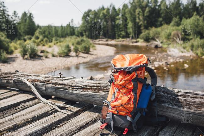 Orange backpack on wooden bridge in forest