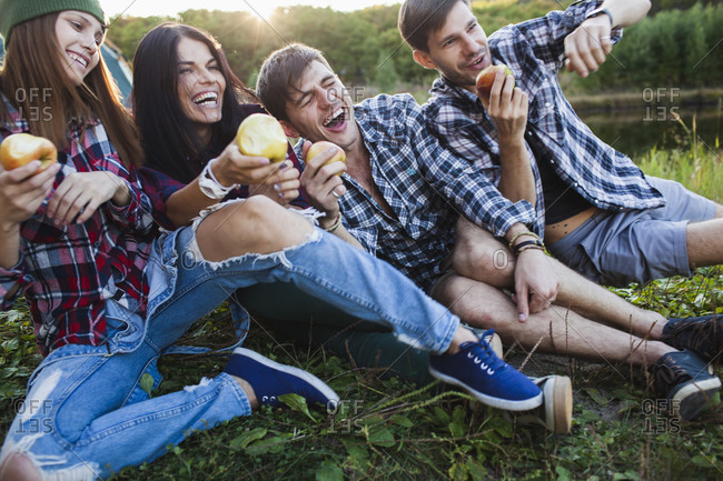 Happy friends falling on each other while having apple in forest