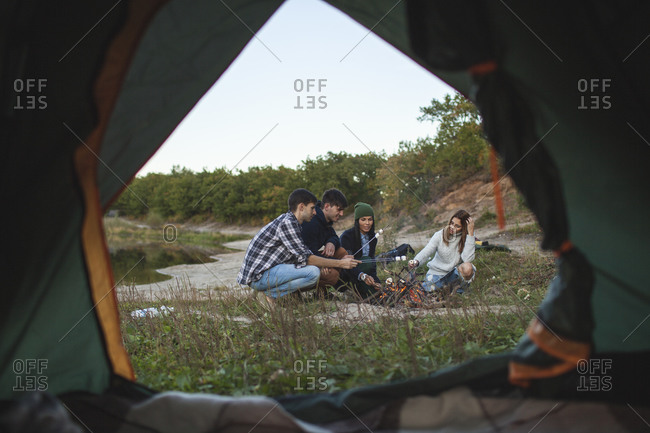 Friends roasting marshmallows seen from tent