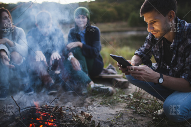 Young man using digital tablet while sitting with friends by bonfire