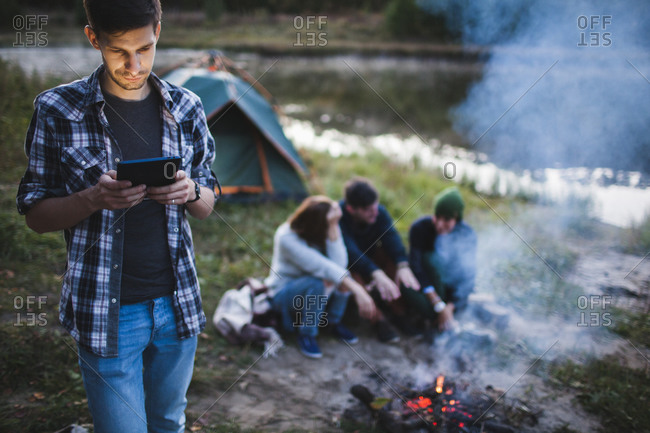 Young man using digital tablet while friends sitting by bonfire in forest