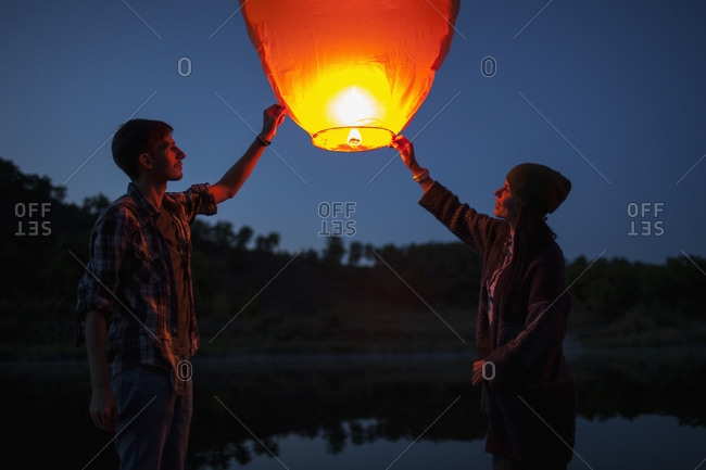 Man and woman releasing paper lanterns at lakeshore