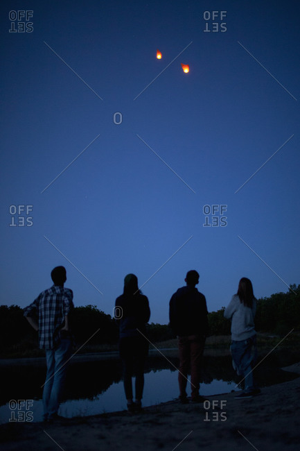 Rear view of friends looking at paper lanterns flying in clear blue sky