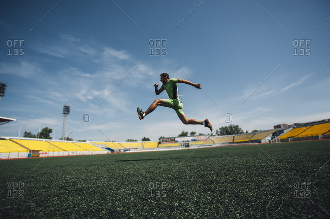 Sporty young man running in stadium during training