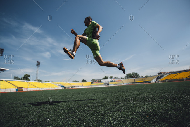 Young male athlete running in stadium during training