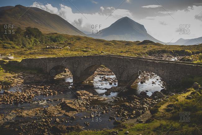 Abandoned arch bridge over stream against mountains, Isle Of Skye, Scotland
