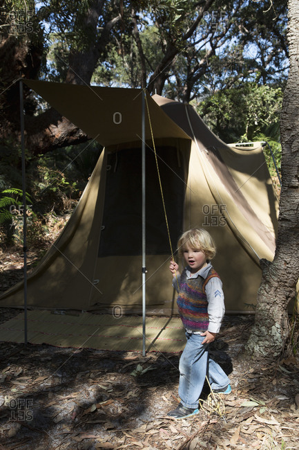 Cute boy holding tent rope in national park