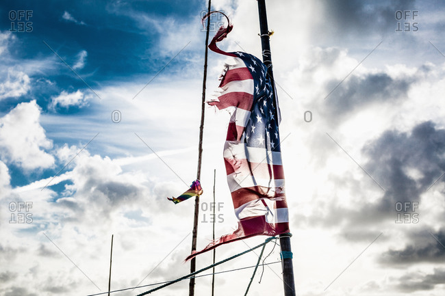 Tattered American flag on pole against cloudy sky, Amrum
