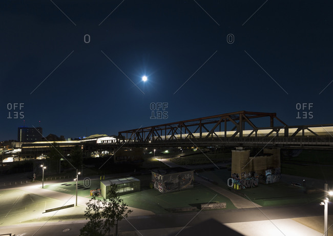 Bridge over illuminated city streets at night, Berlin