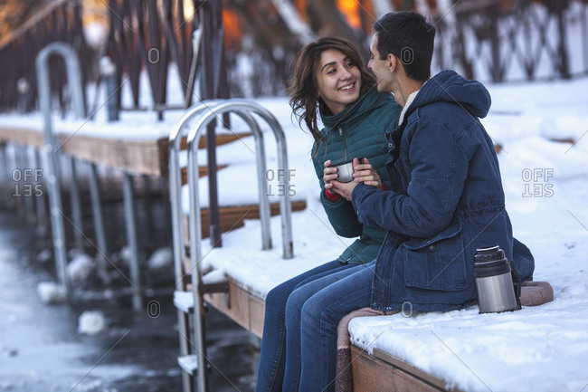 Happy young couple having coffee while sitting on pier