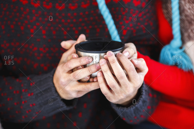 Midsection of young couple holding coffee cup during winter