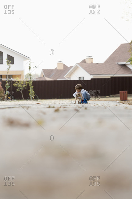 Boy playing with dog on footpath against clear sky