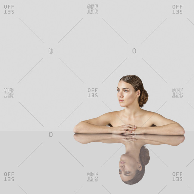 Thoughtful naked woman leaning on table over white background