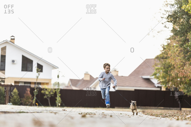 Boy running with dog on footpath against clear sky