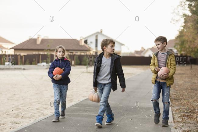 Children holding pumpkins while walking on footpath