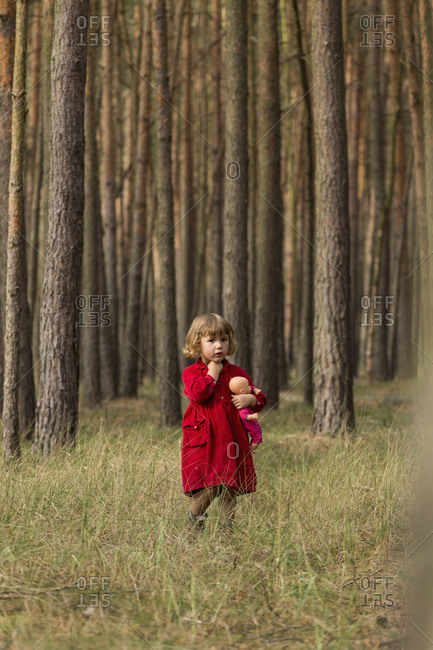 Girl looking away while holding doll in forest
