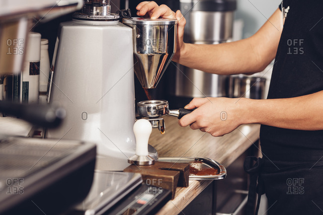 Midsection of barista making coffee in cafe