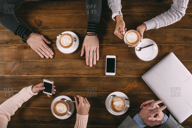 Overhead view of friends having coffee at wooden table in cafe