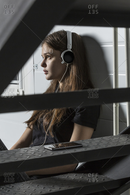 Woman looking away while listening music at studio
