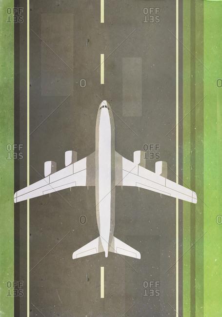 Overhead view of airplane landing on runway